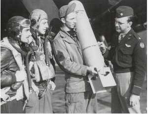 Examining an M46 Photoflash Bomb rated at 700 Million Candles are 1st Lt Robert P Walker (Pilot) 1st Lt William P Mishkho (Navogator) MSgt James M Tenille (Cief Armourer) Major Willis D Locke CO 654 Sdqn 25BG