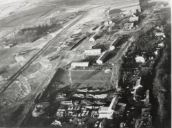 "Part of the complex built on the south side of RAF Watton at Griston village. This view is looking north with Griston on the right of the picture. The aicraft sitting on the ""spectacles"" are Liberators."